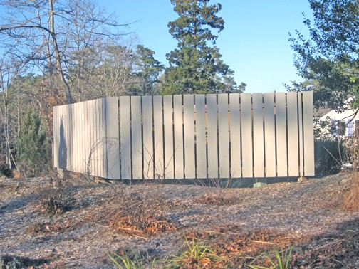 Here's the enclosure, and I'm sure that you can see what I mean... even when the shrub that's planted on the right side, and the trumpet vine that's planted on the corner get growing, it's still two harsh horizontal lines that aren't pleasing.